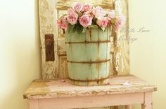 An old ice cream bucket filled w/roses, an old door, and a vintage table- great display for an small, empty, space.