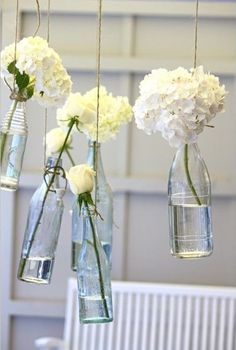 A simple way to make a hanging vase! Clean out empty transparent bottles, tie their necks with thin rope and find a place to hang them! They will look beautiful in a group, with white, pink, red or various flowers in each.