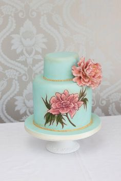 A two tier vintage style sponge cake painted with a sylised peony and decorated with piped gold lustre and a single sugar peony 56 dessert portions from £295