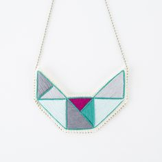 This embroidered geometric necklace is entirely handmade and is the perfect size for everyone. The geometric design is stitched using a beautiful array of colors including mint green, light and dark gray, violet and Pantone's color of the year- emerald green. The pendant is stitched onto cream muslin and then sewn on a thick sturdy felt back with the Astrid Endeavor label attached. It is then hand sewed directly onto a silver ball chain which makes it appear that little silver beads surround…