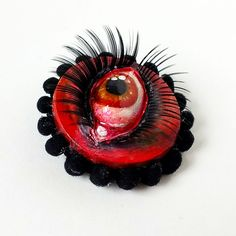 Red Devil brooch - acrylic and paper clay on wood with fabric trim and lashes