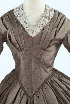 A snuff-brown taffeta day dress, 1840s. the boned and pleated front bodice with deep V waist, rear fastened, pocket slit to one side, Brussels lace collar