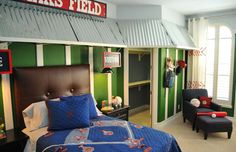 "Baseball themed bedroom - The focal point is the bed, with its glove-inspired, leather-stitched headboard and awning reminiscent of a dugout. The walls, appropriately painted turf green with gloss white trim, feature hand-painted signs indicating ""home"" and ""visitor."" The storage area is actually a functional locker system beneath which sits a dugout bench. Framed baseball memorabilia and baseball-inspired bedding complete the theme."