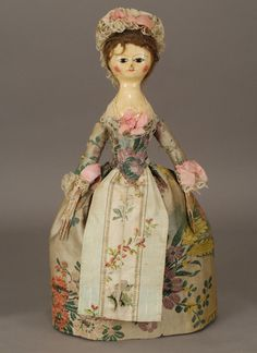 18th century doll with pretty brocade gown and apron.