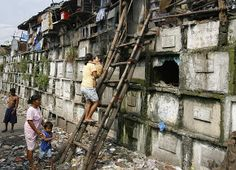 Residents climb into their houses atop gravestones inside a cemetery in Manila, the Philippines. Many poor urban dwellers make their homes in public cemeteries, converting abandoned tombs and mausoleums into houses.