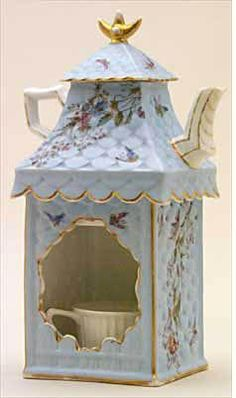 Trenton Teapot.  Blue shell-grained square stand with overhanging scalloped roof; teapot has white handles & spout and forms turret to the house; floral trim!