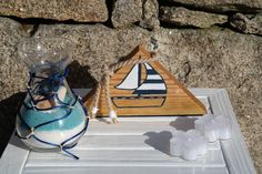 My Boat é uma decoração da ArteNatis constituída por:  - Uma peça triangular em madeira de carvalho, com acabamento de verniz mate, e realizada com uma pintura realizada à mão de um barco;  - Um recipiente decorativo em vidro, preenchido com pó decorativo e conchinhas do mar;  - Duas velas decorativas brancas.