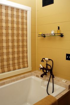 A bathroom tub in a 1920's cottage recreation. The walls are painted pine with plumbing fixtures consistent in appearance to the time period. For more of this home visit this pin board. - John - http://pinterest.com/northtwinbuild/ntb-1920-s-lake-cottage-recreation-in-phelps-wi/