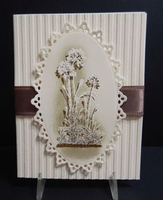 """By Mary (jandjccc at Splitcoaststampers). Stamped in VersaMark and embossed in white. Then stamped same stamp in brown, offset from the first stamping. Sponged. Die-cut """"frame."""" Card front dry-embossed in Stampin' Up stripes embossing folder. Ribbons added."""