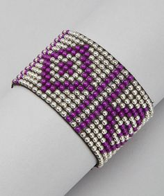 Sometimes the jewel box needs a little edge. This stretchy bracelet does the trick with spherical beads of silver and purple arranged with geometric flair.