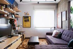 Sala de televisão com sofá cinza, parede de concreto e piso de taco.