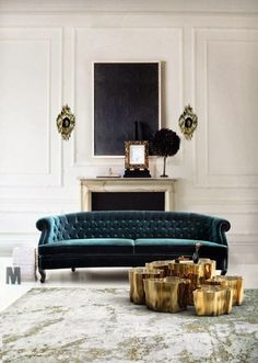 Brutalist sconces flank an elegant mantel with modern art. A velvet tufted sofa, abstract rug and modern gold coffee table complete the scene.