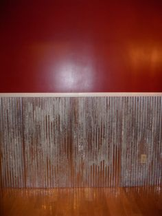 My husband is so crafty! We cut 8ft barn tin in half and screwed it to the wall. Then we added molding on top to give it a finished look. It is a great idea for a house with kids! It holds up to all kinds of abuse. The paint color is Front Door Red from Lowes.