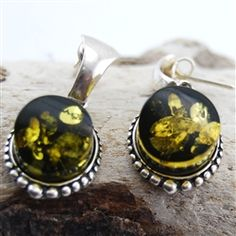 Incredibly beautiful Baltic green amber with inclusions is cradled by handcrafted silver. Each set of post earrings are one of a kind and will be a cherished piece. #amber #fashionjewelry