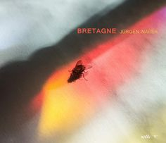 Bretagne  One fly does not a picture book make. Spiritually sunning itself on the altar cloth in the refracted light of a Breton church window, though, the fleeting assumes a form. A form that, in this book, alternates from liquid to solid and back again.