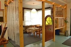 "I love the family corner structure. The sheer curtains, frame, and child-sized door make it feel cozy, and ""set apart"" from the rest of the class, but the children are still visible. It looks like it's own room. I want one."