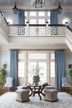 Two story entry with stunning Chinoiserie stair rail design and highlighted with blue curtains edged in Greek key tape via Chinoiserie Chic: Classic Blue and White Chinoiserie