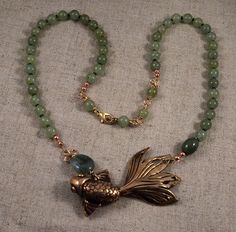 A hollow cast bronze goldfish with aventurine