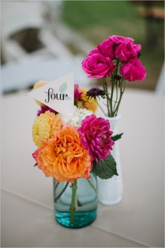 table number flags with hot pink and orange centerpiece florals