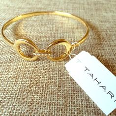 Tahari Gold Double Circle Bangle Bracelet Tahari Gold tone Essentials Double Circle Bangle Bracelet his simple bracelet features clear rhinestones on the center.  Dimensions 4 x 3.9 x 0.7 inches Brand new, never been worn. NWT Retail $38 Tahari Jewelry Bracelets