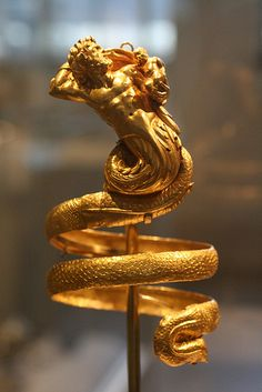Male Triton Gold Armband Greek, Hellenistic ca, 200 B.C. This imposing serpentine armband represents a male triton holding a small winged Eros. The hoops behind the tritons' head were used to attach the armband to the sleeves of a garment, for otherwise, its weight (over 6 1/2 ounces) would have caused them to slip down the arms.
