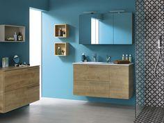Envie d'une déco bleue ? Choisissez des meubles de salle de bain en bois naturel pour un rendu lumineux (chêne Arlington). Astuce déco : pensez au gris pour le sol et le carrelage, cette couleur plus sombre jouera les contrastes et apportera un maximum de lumière à votre espace bain. – liberty de Sanijura