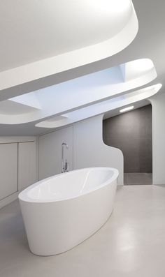 This modern bathroom has a white standalone bathtub that sits below a large, recessed skylight. Rectangular grey tiles are used in the portion of the bathroom where the toilet is.