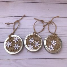 Handmade Mason jar lid burlap ornaments with white snowflakes. These ornaments are made from the small Mason jar lids. They measure approximately 2 and 3/4 inches in diameter. The ornaments are hung using the jute twine loop that is attached to the Mason jar lid. The middle piece is wrapped in a brown burlap material. The snowflakes are made of a thick cardstock. These ornaments will add the perfect touch of rustic to your shabby chic or cabin themed holiday decor. They would also make a…
