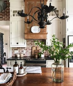 gorgeous farmhouse kitchen with wrought iron chandelier, brick backsplash accent wall, white cabinets to the ceiling with oil rubbed bronze fixtures. large wood butcher block island. I love it all!