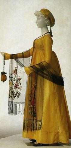 """Yellow silk taffeta dress(1803) w/black silk net shawl w/polychrome floral embroidery& yellow & green silk knit pineapple reticule c.1800 w/trimmings of silver beads & tassels"" https://janeaustensworld.wordpress.com/category/fashions/page/13/."