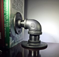 Industrial pipe bookend made from unfinished iron pipe fittings with a natural gunmetal color. These bookends are larger and heavier than similar ones you will find on Etsy. Available in 4 different sizes.  - Can be used on the left or right side. - Clear coat enamel to protect against rust, corrosion, tarnishing and chipping. - Dimensions of Small bookend: Height to top of elbow is 3.5. Height to top of side flange is 4.5. - Dimensions of Medium bookend: Height to top of elbow is 4. Height…
