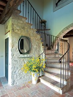 Love the stone wal, rod iron railing and the circular staircase, not to mention the arched entry area...gorgeous!