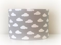 Handmade drum lampshade in  Grey & White Cloud  fabric, produced on the south coast of England.  Available sizes: . . . . . . . . . . . . . Diameter - 20cm X 18cm high. Diameter - 30cm X 21cm high.  Beautiful hand rolled lampshade for use with a ceiling fitting or table lamp. Please select your preference to ensure correct placement of pattern.  The lampshades are made to order, so please allow 1-2 weeks for dispatch. Please note due to each one being handmade, pattern placement may vary,...