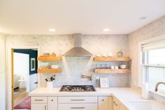 Funky, raw wood floating shelves lend a bit of whimsy and warmth to a bright, white, and modern kitchen design. 1960s Kitchen, Mid Century Modern Kitchen, New Kitchen, Brass Kitchen, Midcentury Modern, Home Design Decor, House Design, Rental Kitchen, Diy Carpet
