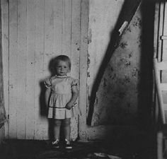 Ralph Eugene Meatyard • Small Girl Standing Next to Wall with Peeling Wallpaper
