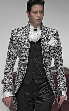 Bräutigam Anzug, Redingote mit Posamenten-Stehkragen, schwarz/silber, aus Brokat-Stoffen, koordiniert mit Hose, schwarz, aus Taft, Weste, schwarz, aus Brokat-Stoffen, Amadeus und Einstecktuch aus Spitzen, Nadel mit Kamee, schwarz, mit Edelkristall und weißes Hemd aus Taft mit Volants.