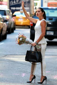Olivia Munn tight trousers, peplum sleeveless top and killer heels street style holding flowers hailing a cab