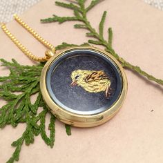 This is too cute! A tiny hand embroidered yellow warbler bird set in a glass locket necklace!    https://www.etsy.com/listing/252057639/yellow-warbler-bird-necklace-embroidered