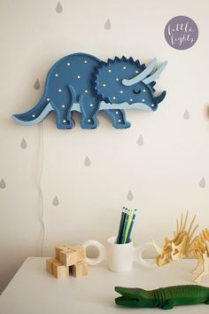 Our Little Lights Triceratops Dinosaur Lamp is a unique, handmade piece of kids' room decor designed to fill any nursery or playroom with the glow of childlike joy. Dimmable LED lights allow you to adjust the mood for reading, playing, or sleeping. The perfect modern gift for a baby shower, kids' birthday, or Holiday; this high-quality night light is made from natural pine wood, making it as durable as it is beautiful. Your little one is sure to fall in love with this work of art. Get one today! Nursery Themes, Room Themes, Nursery Ideas, Nursery Decor, Room Ideas, Dinosaur Bedroom Decor, Dinosaur Nursery, Animal Nursery, Baby Boy Rooms