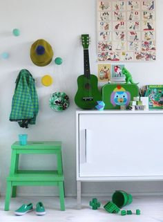 Slide 4 - The monochromatic color combination of green in this modern style room offers a sense of fun, renewal, harmony and alleviates anxiety. This emerald green is such an amazing and classic color that has been utilized very appropriately by using as an accent color for the stool. The jacket, guitar, shoes and other toy items used as accessories are adorable and cute.  I like the use of the small guitar hung on the wall which suits the mood of a musician toddler boy.