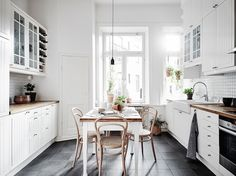Light wood Thonet chairs in the kitchen of a magnificent white Swedish apartment