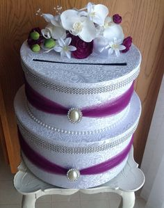 Two tier card box covered in your choice of satin. Matching sashes, brooches , pearls, sparkle ribbon, and flower orchid cluster on top. Bottom box