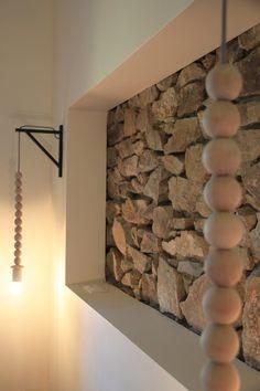 tête de lit en pierre avec un caisson rectangulaire pour cette chambre beige avec suspension applique en perle en bois sur support triangle noir façon scandinave