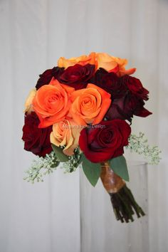 Orange, yellow and burgundy roses for a bright wedding bouquet.