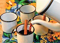 Cestas de vime e potes coloridos vão caracterizar ainda mais a mesa, além de você poder usar peneiras grandes de madeira para decorar. Para beber, um quentão vai bem, né? Ou até mesmo um chocolate quente, para quem preferir. O bule e as canecas de metal esmaltado são uma fofura, tem tudo a ver com o espírito junino e são eficientes para manter a bebida bem quente. A canela em pau dá um charme na hora de servir, além de ser gostosa!