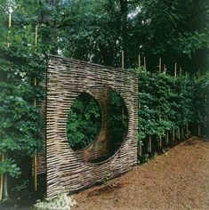 willow panel with circle cutout, set within a hedge at the Mill House in Vastra Karup, Sweden, by architect Gert Wingardh
