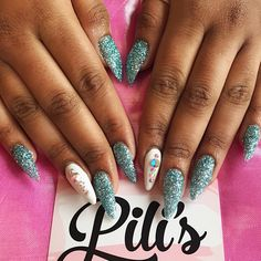 Stiletto shaped acrylic nail extensions with frosty blue glitter white accent nails and Swarovskis