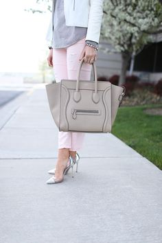Shop this look on Lookastic:  http://lookastic.com/women/looks/tote-bag-jeans-long-sleeve-blouse-biker-jacket-pumps/8687  — Grey Leather Tote Bag  — Pink Jeans  — Grey Vertical Striped Long Sleeve Blouse  — White Leather Biker Jacket  — Clear Rubber Pumps
