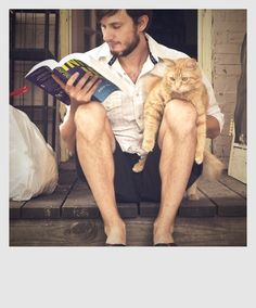 A great book read by a great man holding a great cat.