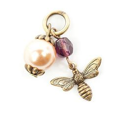 The Lenny & Eva Bee Charm features a small bee in antique brass with outstretched wings under a colored faceted bead. The charm also has a pearl bead delicately secured by decorative antique gold filigree detail. Like all Lenny & Eva jewelry, the charms are handcrafted and lead-free. Each piece may vary. $9.95 at Quirks of Art. *Customize bracelet & cuffs. *Friendship bracelets